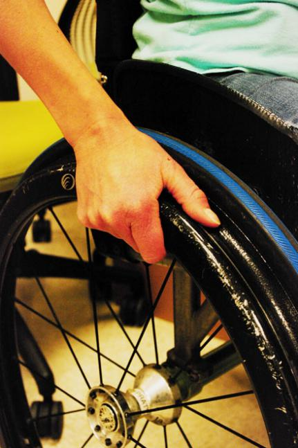 wrist and hand holding rim of wheelchair wheel
