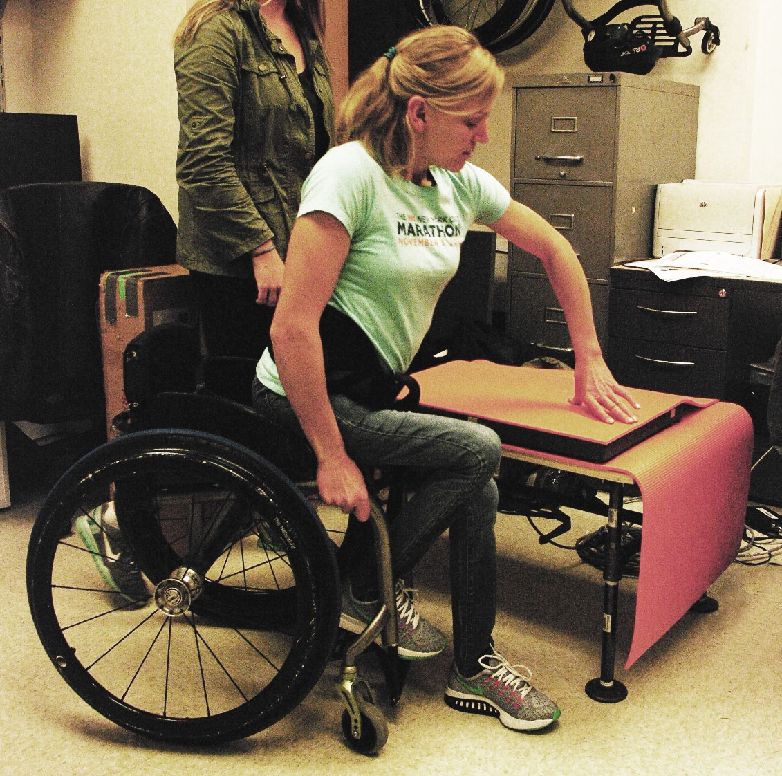 woman moving from a wheelchair to a table