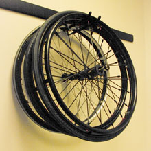 extra wheelchair wheels hanging on a wall